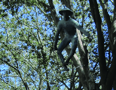"On Lemon Street in Lakeland, Jerzy Kedziora's ""Feng Shui"" of coldcast bronze is suspended between the trees."