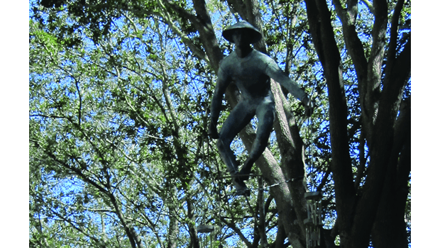 "On Lemon Street in Lakeland, Jerzy Kedziora's ""Feng Shui"" of coldcast bronze is suspended between the trees."