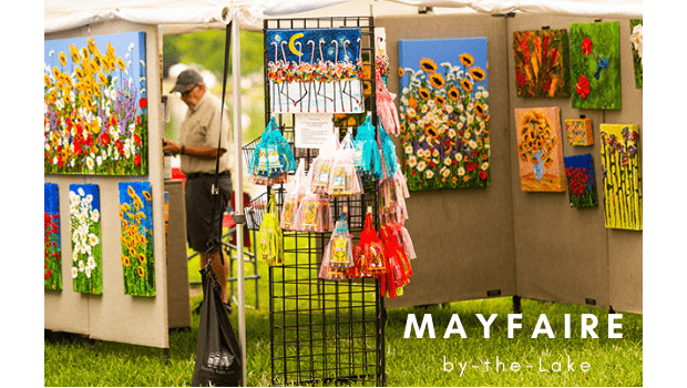 Background photo of vendor booth at Mayfaire. Text is Mayfaire by-the-Lake.