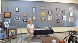 Vicki Alley smiling in the Gray Gallery in front of a wall of her artworks.