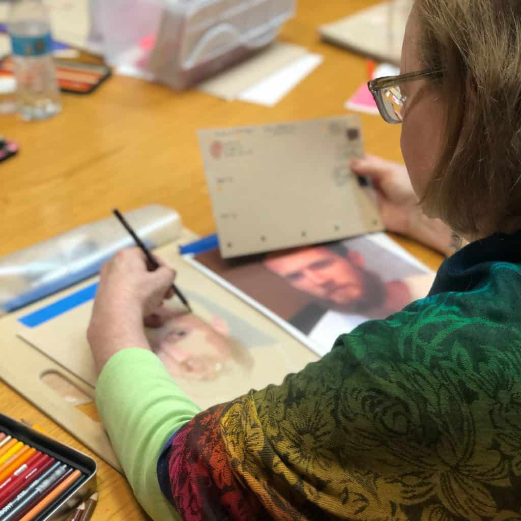 Left-handed girl sketching a portrait of a man from a photograph