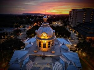 Photo at sunset of the Old Polk County Courthouse lit in yellow by David Butters