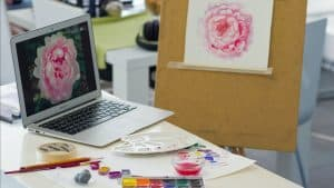 photo of a laptop computer with a rose and of an easel with a sketch of a rose