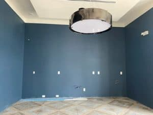 Blue room with tile floor and large overhead light.
