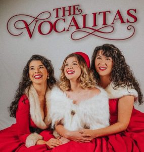 3 women in red Christmas outfits. The Vocalitas